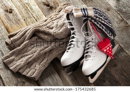 The white ice skates on old wooden boards - stock photo