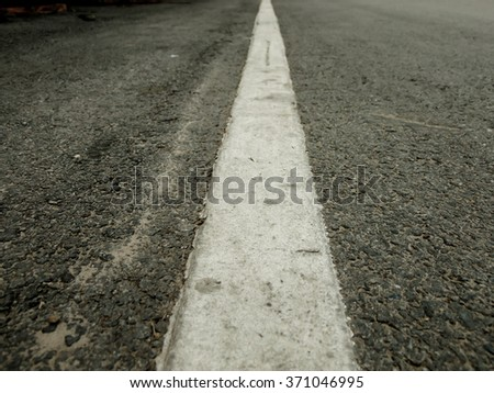 The white line on the road with tree and sky background. - stock photo