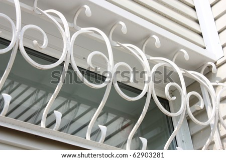 The white metal forged carved lattice at a plastic white window - stock photo