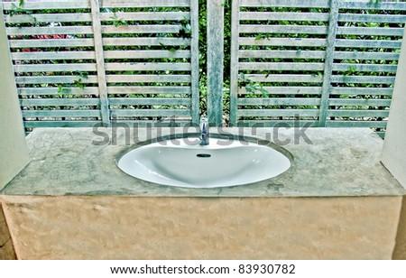 The White modern ceramic handbasin and chrome tap - stock photo