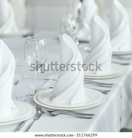The white napkin nicely folded on the plates, serving a celebratory banquet - stock photo
