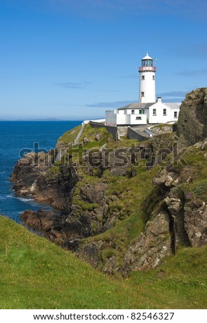 The white painted lighthouse at Fanad Head, Donegal, Ireland stands on a cliff top above the blue Atlantic Ocean, a safety beacon for shipping in the dangerous coastal waters around the rocky shores. - stock photo