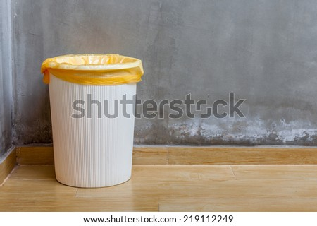 The white plastic bin with orange bag on wooden floor with exposed cement background, for cleaning and recycle. - stock photo