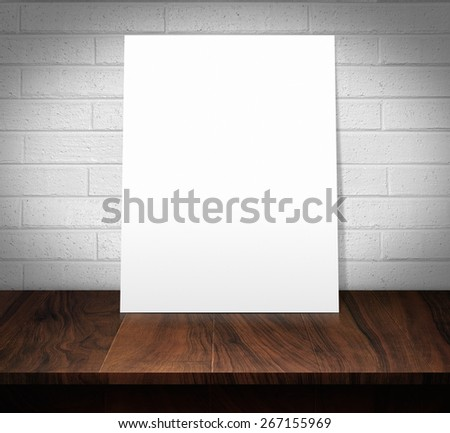The white poster on a wooden table with a white brick wall