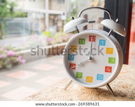 The  white retro alarm clock with colorful number is showing 8 o'clock on wooden background and window glass - stock photo