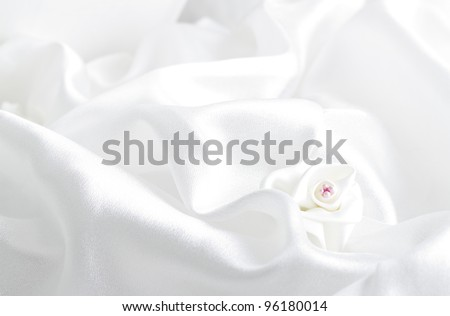 The white satin fabric and a rose - stock photo