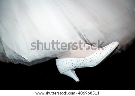 The white Shoe on the leg of the bride in a white dress on a black background. Foot in an elegant Shoe. - stock photo