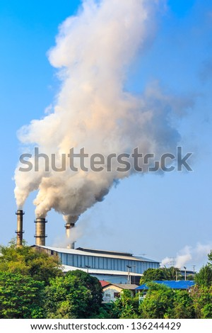the white smoking chimneys of a factory against a blue sky. - stock photo