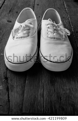 The white sneakers on vintage wooden floor; Selective focus on white sneakers ; Black and white tone