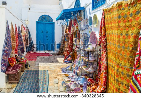 The white walls covered with the colorful rugs for sale and many local souvenirs on each taste, Sidi Bou Said, Tunisia. - stock photo