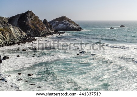 The white wash of ocean waves pound the shoreline along the Pacific Coast Highway in California. - stock photo
