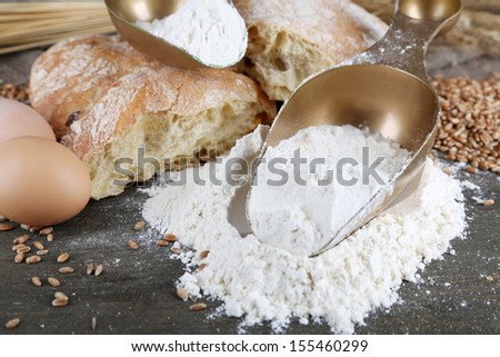 The wholemeal flour in scoops on wooden table