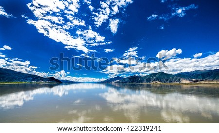 The wide and calm Yarlung Tsangpo river under the blue cloudy sky in Tibet, China