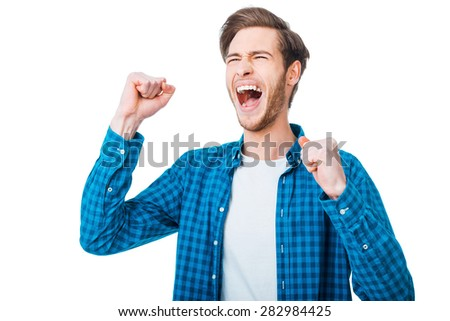 The win is in my pocket. Excited young man keeping arms raised and expressing positivity while standing against white background - stock photo