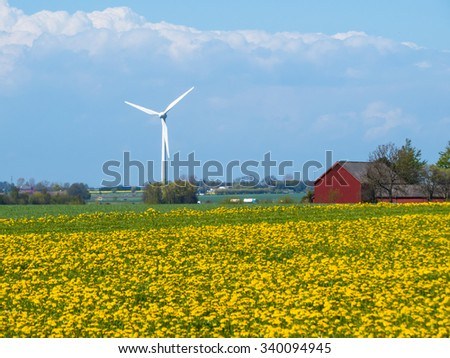 The wind generator on the blossoming fields in south Sweden - stock photo