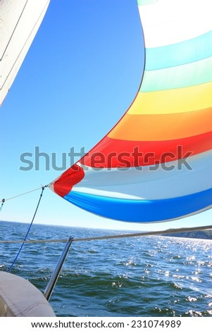 The wind has filled the spinnaker on sailing yacht. Detail of a colorful sail against the deep blue sky. - stock photo