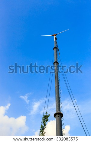 The wind turbine in the blue sky.It's a device that converts kinetic energy from the wind into electrical power.