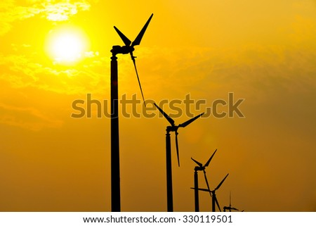 The wind turbines silhouette generating electricity in the sunset sky. - stock photo