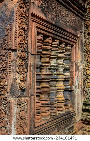 The window of the hinduistic Banteay Srey Temple at the Angkor Wat area dates back to the 10th century and is dedicated to Shiva. - stock photo