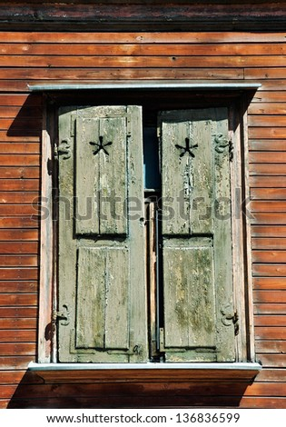 The window of the old wooden  shutters on the background of wooden walls - stock photo