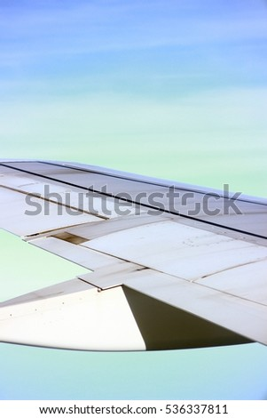 The wings of the plane that was flying in the sky. The background is blue sky.