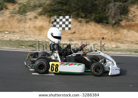 The winning go kart doing a lap of honour with the chequered flag - stock photo