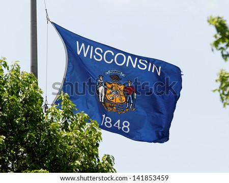 The Wisconsin state flag waving in the wind. - stock photo