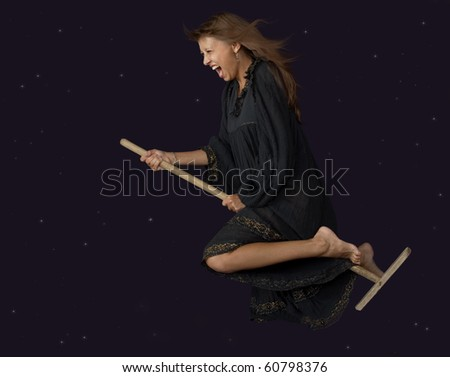 The witch flies on a mop at night - stock photo
