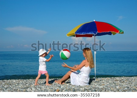 The woman and the child sit under an umbrella and play a ball at coast