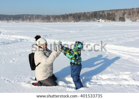 The woman and the little boy in a color jacket playing on snow in the winter - stock photo