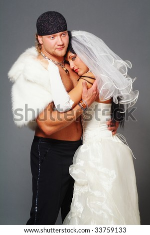 The woman and the man in a wedding dress on a grey background
