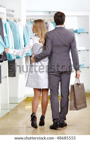 The woman and the man leave clothes shop - stock photo