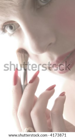 The woman applies cosmetics on the face. - stock photo