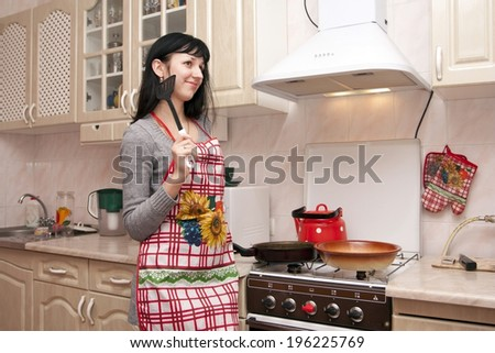 The woman at a plate prepares to eat on kitchen