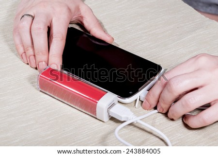 The woman charges the smartphone by external battery. - stock photo