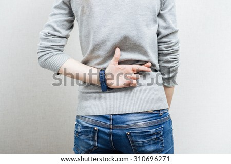 The woman crossed her fingers. On a gray background. - stock photo