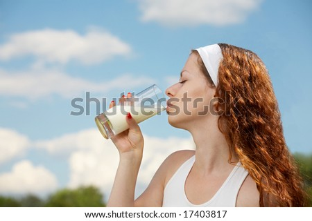 The woman drinks milk against the blue sky
