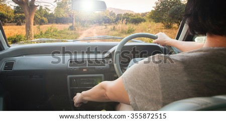 The Woman Drives a car with urban background