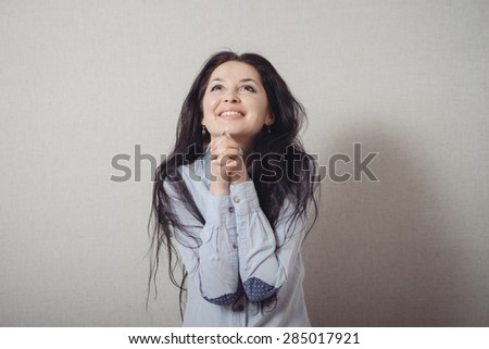 The woman folded her hands in prayer. On a gray background. - stock photo