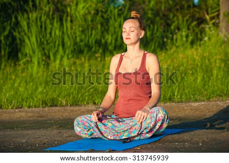 The woman girl is doing yoga exercises on the river bank - stock photo