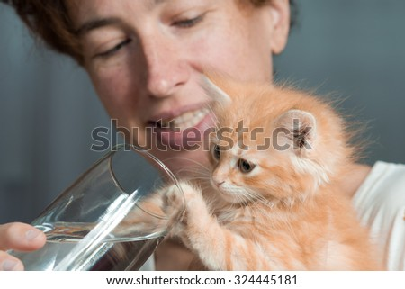 The woman gives a red-haired fluffy kitten to drink water from a glass. 