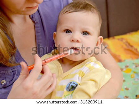 The woman gives to the sick baby medicine by means of the batcher. Treatment