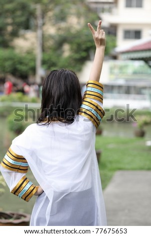 the woman happy in behind victory,active in the park - stock photo