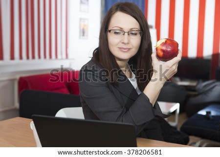 the woman has a bite at work as apple  - stock photo