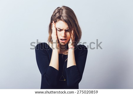 The woman has headache, migraine. On a grey background - stock photo