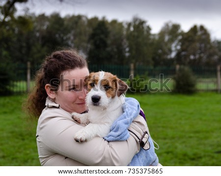 The woman hugs a small dog in a towel Soaking puppy jack russell terrier.