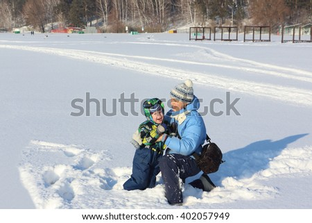 The woman in a blue jacket and the little boy laughing     on snow    - stock photo