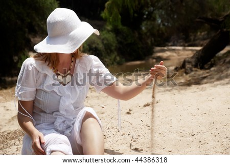 The woman in a hat playing with sand
