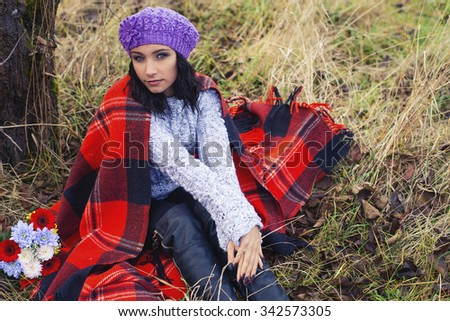 The woman in a plaid has a rest outdoors, the first frosts