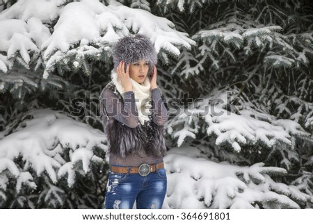 The woman in an elegant scarf against the wood and snow in the winter